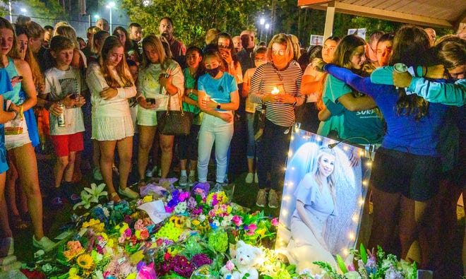 Classmates, friends and neighbors gather around a memorial to 13-year-old Tristyn Bailey during a vigil at the Durbin Crossing community center on Monday, May 10, 2021. A 14-year-old boy has been charged with second-degree murder after Tristyn's body was found on Sunday.