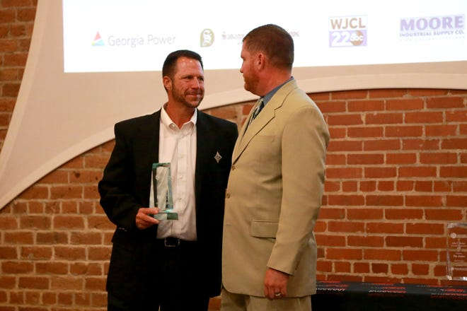 Calvary Day School athletics director Chad Griffin, left, who also coaches the boys and girls soccer teams and the girls flag football team, receives the Savannah Sports Council Award of Excellence from director Rob Wells on Tuesday during the annual Georgia Power Sports Awards Luncheon.