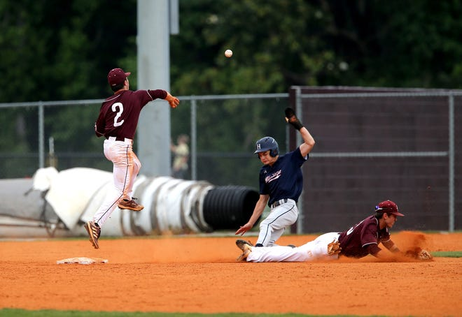 Benedictine's Kam Edge gets airborne as he turns a double play during a state playoff game against Heritage on May 10.