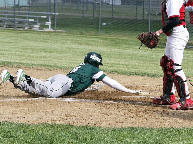 Connor Oatley of Mendon slides head-first into home plate to score a run against Bangor on Monday afternoon.