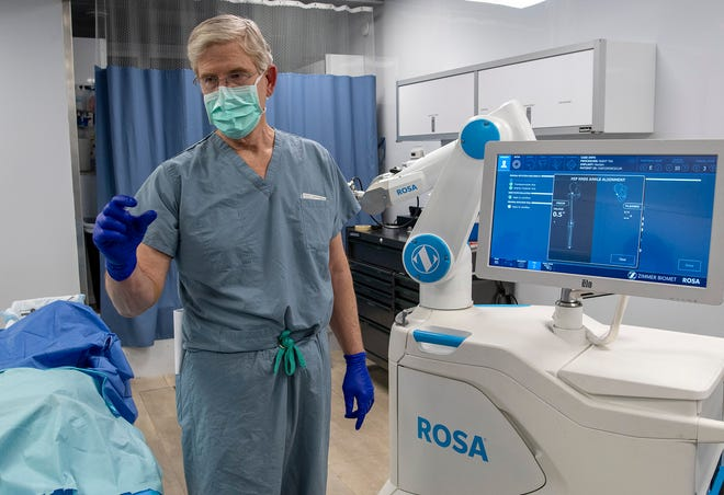 Dr. David Ayers describes how the ROSA Knee robotic technology helps surgeons during a training session Monday.