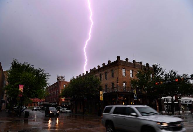 A lightning bolt strikes in the sky south of downtown Abilene on Tuesday. Heavy rain accompanied the late morning storm