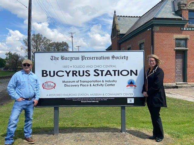 This week a new sign was put in place on Rensselaer Street at the front of the Toledo and Ohio Central railroad depot by John Cauvel (left)  while Kriste Slagle, First Federal Community Bank's marketing director, visits it for the first time. The bank sponsored the project.