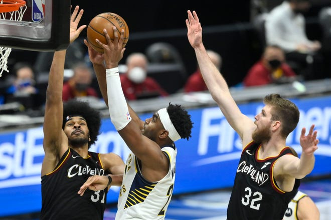 May 10, 2021; Cleveland, Ohio, USA; Indiana Pacers guard Kelan Martin (21) drives between Cleveland Cavaliers center Jarrett Allen (31) and forward Dean Wade (32) in the fourth quarter at Rocket Mortgage FieldHouse. Mandatory Credit: David Richard-USA TODAY Sports