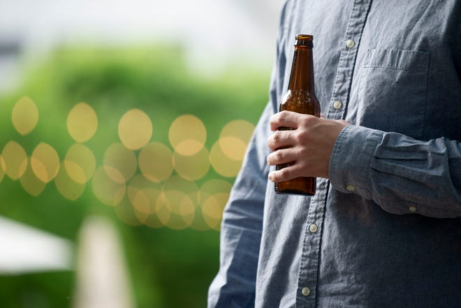 In this photo illustration, a man holds a beer in a public area.