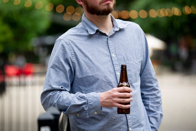 In this photo illustration, a man holds a beer in a public place.