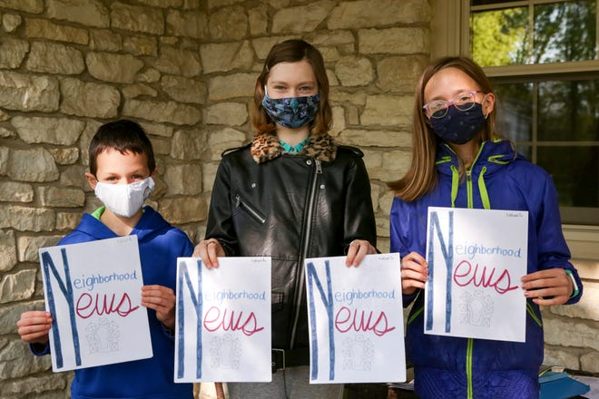 William Foote, 8, Izzy Bechler, 11 and Rebecca Foote, 11, pose for a photo with Neighborhood News, a weekly newspaper the group of neighbors put together for their cul de sac, Friday, May 7, 2021 in West Lafayette.
