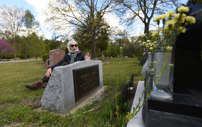 Beth Hubbell of Haslett sits near the headstone of her late husband Richard Hubbell on Tuesday, May 11, 2021, at Glendale Cemetery in Meridian Township. She is dissatisfied that another headstone has been placed less than two feet from her husband's marker.
