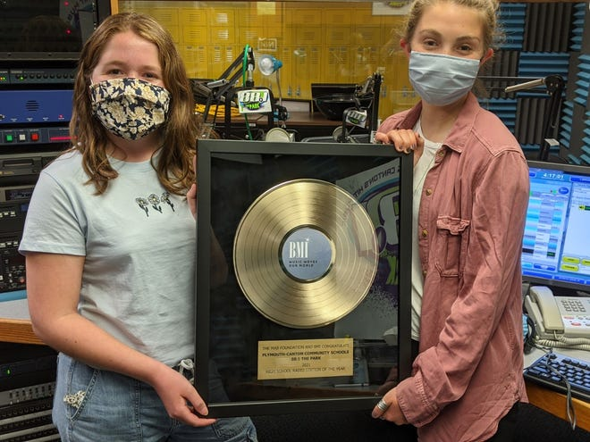 WSDP student on-air personalities Lily Mahnken and Emma Johnston (both juniors at Plymouth High School) hold the station's most-recent Station of the Year award.