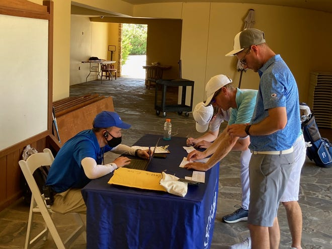 Garrett Evert of the Southern California Golf Association helps three players check their scorecards during a local qualifying tournament for the U.S. Open at Classic Club in Palm Desert. Players were not allowed to sit at the table and could not gather around a leaderboard at the event because of COVID-19 restrictions, and Evert was the only official checking cards for the round.
