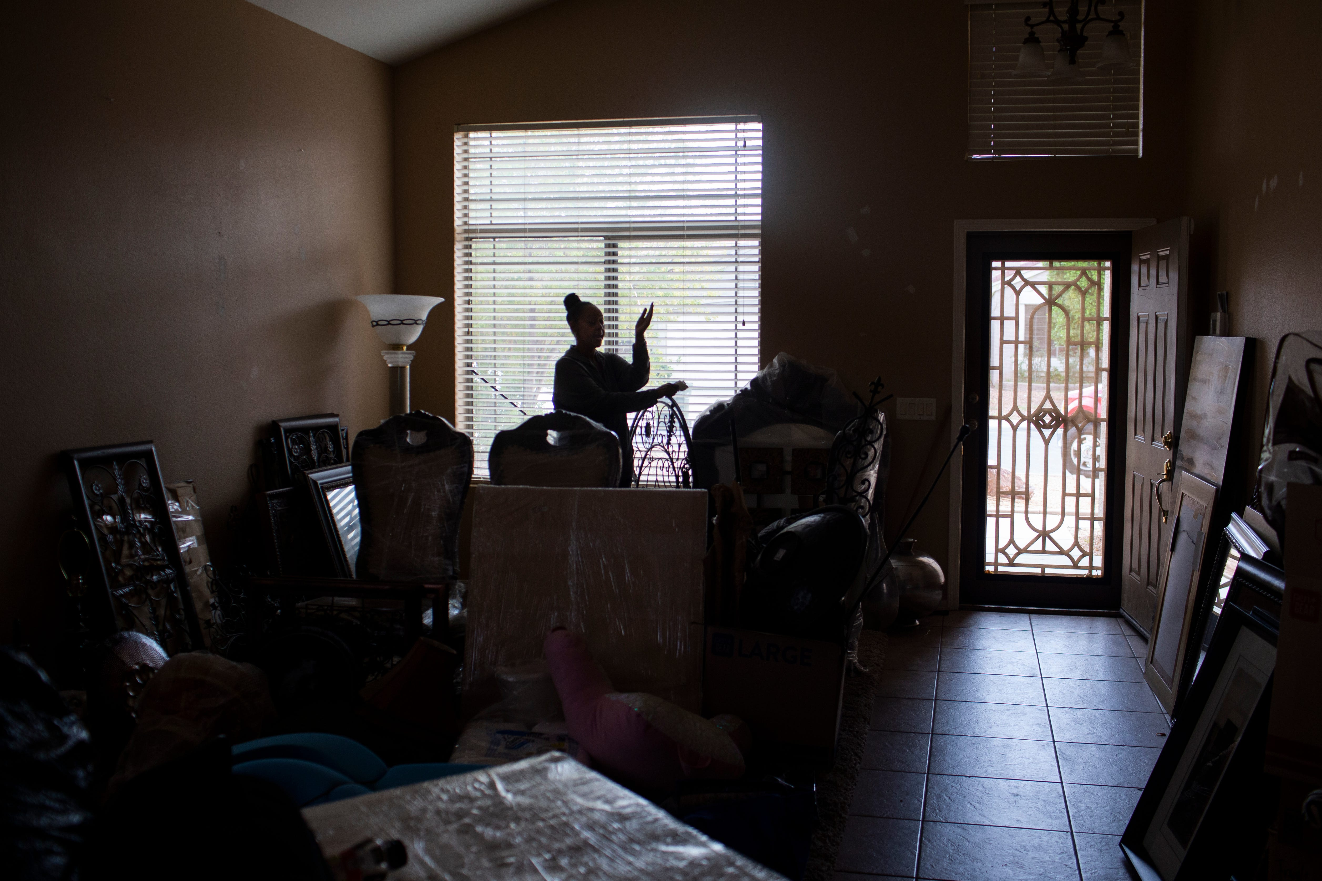 Sylvia Haysbert-Stevens stands inside her living room and packs her belongings that sheÕs preparing for a storage unit since she has been evicted from the home she was renting in El Mirage, Ariz. on Mar. 11, 2021. Despite a moratorium preventing landlords from evicting tenants during the COVID-19 pandemic, a court ordered Stevens to vacate the El Mirage home she had been living in with her daughter and granddaughter.