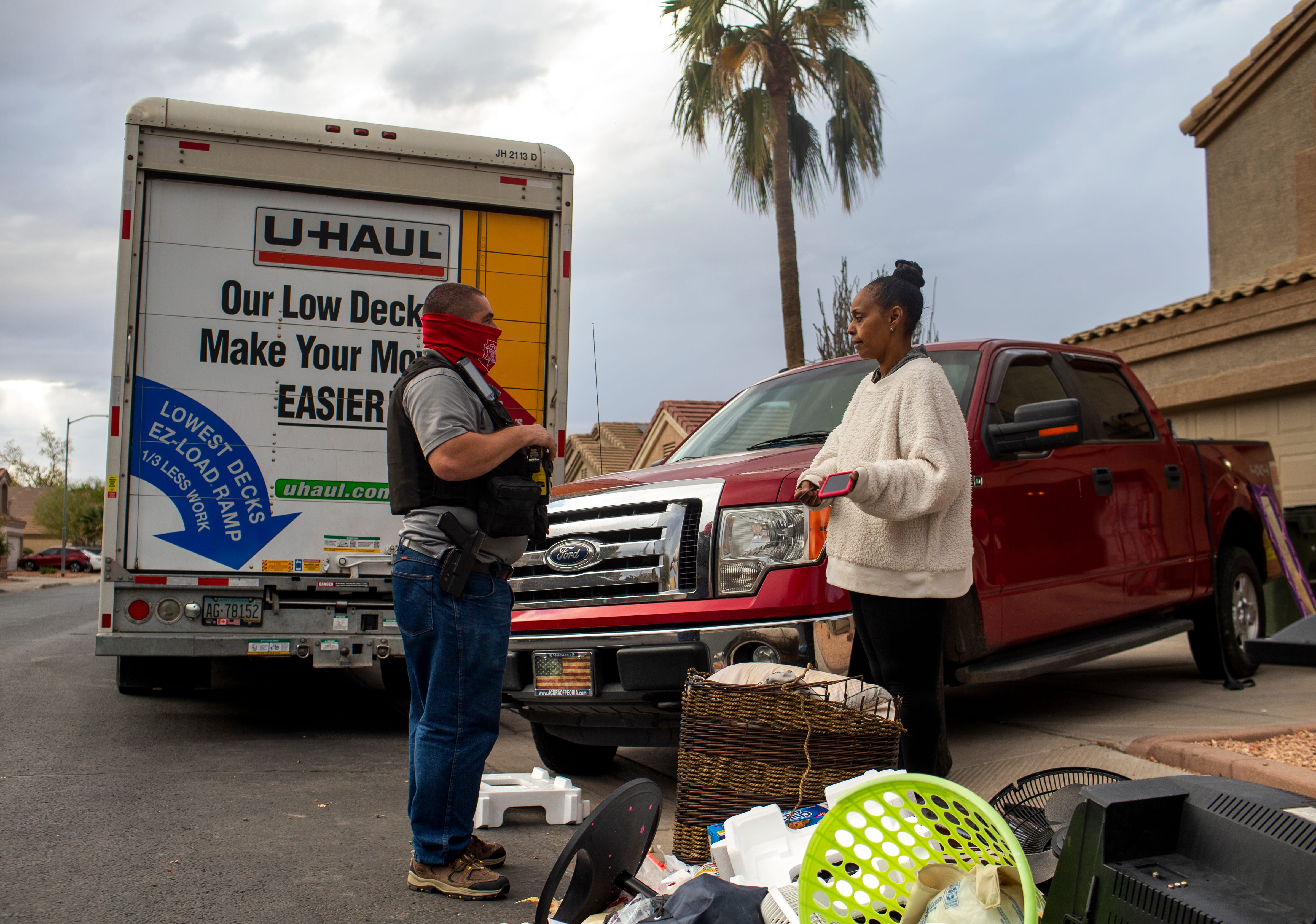 A constable who did not wish to be identified (left) asks Sylvia Haysbert-Stevens how much longer she will need to move her belongings out of a home she had been evicted from in El Mirage on March 11, 2021. Despite a moratorium preventing landlords from evicting tenants during the COVID-19 pandemic, a court ordered Stevens to vacate the El Mirage home she had been living in with her daughter and granddaughter.