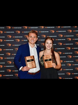 Founders of Dam Worth It, Nathan Braaten, left, and Taylor Ricci, receive an award at Oregon State.