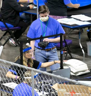 Maricopa County ballots from the 2020 general election are examined and recounted by contractors hired by the Arizona Senate in an audit at the Veterans Memorial Coliseum in Phoenix on May 11, 2021.