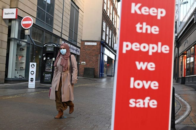 """A pedestrian wearing a face mask or covering due to the COVID-19 pandemic, walks past a sign reading """"Keep the people we love safe"""" in York, north west England on January 6, 2021, on the second day of Britain's national lockdown to combat the spread of COVID-19. (Photo by OLI SCARFF/AFP via Getty Images/TNS)"""