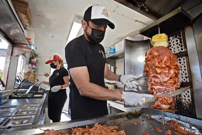 Miguel Ángel Escoto slices beef off a vertical rotisserie inside La Cabañita taco truck as his wife Erika Martinez roasts jalapeño peppers on May 7, 2021. This family opened their food truck business amidst the COVID-19 pandemic.
