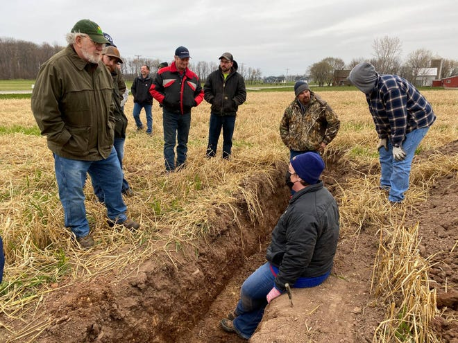 Jamie Patton (in soil pit) from UW-Madison's Nutrient and Pest Management Program talks with farmers about biomass created by cover crops at a Peninsula Pride Farms Conservation Conversation field event on April 28 at Mike Vandenhouten's farm in Brussels, Wis.
