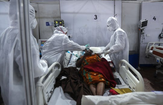 Health workers water patients at BKC Jumbo Field Hospital, one of the largest COVID-19 facilities in Mumbai, India, Thursday, May 6, 2021.