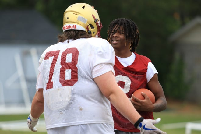 Marquis Groves-Killebrew chats with a teammate during Brookwood's spring practice on Tuesday.
