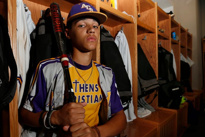 Athens Christian's Seaver King poses for a photo in his track uniform with his baseball uniform over his shoulders inside the Athens Christian baseball locker room on Wednesday. The senior manages to excel at both springtime sports.