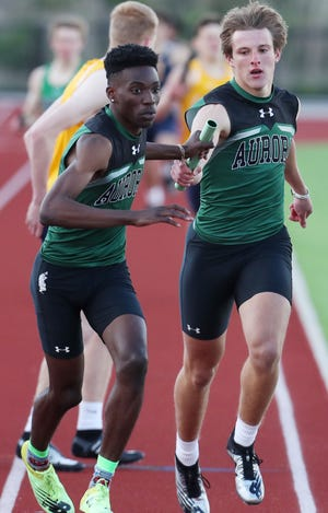 Aurora's Noah Harrison takes the baton from Aiden Henderson in the boys 4x400 relay at the Suburban League track & field championships. The relay won the regional championship Friday in Austintown.