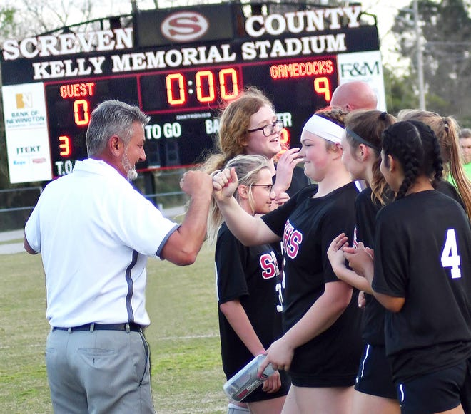 Lady Gameocks soccer head coach Terry Markovcic fist bumps with sophomore Shay Sasser after Screven County earns a 9-0 victory over visiting Bryan County on March 23 to claim the program's first-ever region championship. Markovcic has been voted the Region 3A Coach of the Year for 2020. Six of his Lady Gamecocks made the region first team after an 18-2 season.