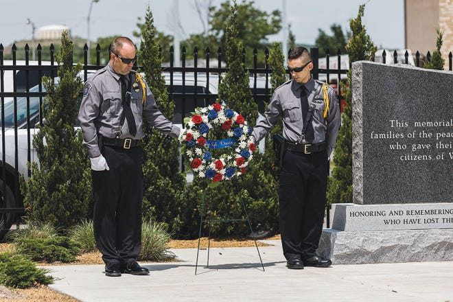 An honor guard flanks a memorial wreath for Washington County Cpl. Kyle Davis during Wednesday's ceremony .