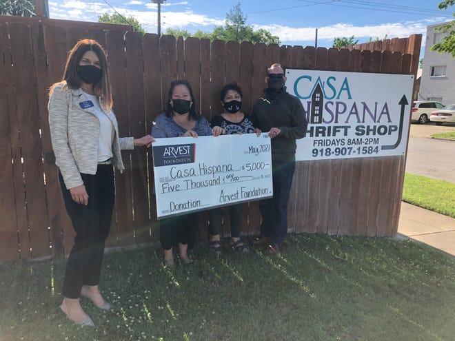 Arvest bank president Kim Adams presents the check to Casa Hispana executive director Mili Cappelletti and board members Clarissa Rowley and Jeff Birk.