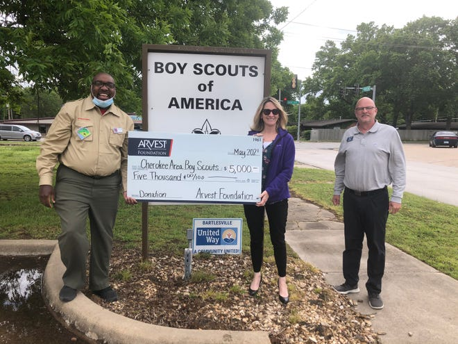 Arvest loan manager David Nickel and mortgage manager Sonya Reed present a check to Cherokee Area Council Boy Scouts Executive Director Philip Wright