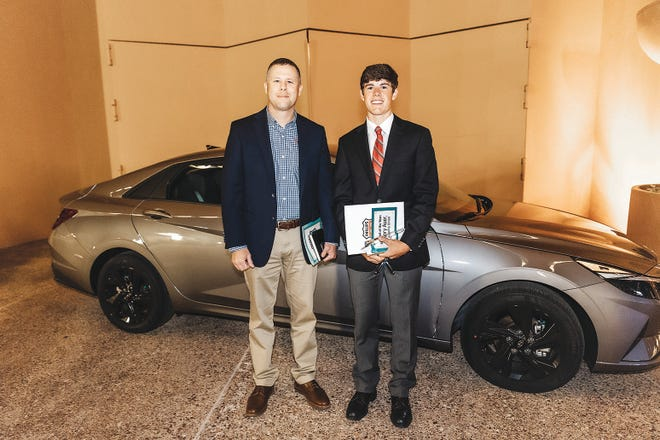 Henry Auer, right, a senior at Oklahoma Union High School, stands with Tatton Manning of Patriot Auto Group in front of the new 2021 Hyundai Elantra that Auer won as the Student of the Year.
