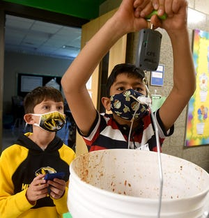Cedar Ridge Elementary School third grader Parth Gupta, 9, weighs a bucket of food scraps that will be used as compost as Eli Martin, 9, keeps track of how many pounds of food scraps they are recycling at the school.