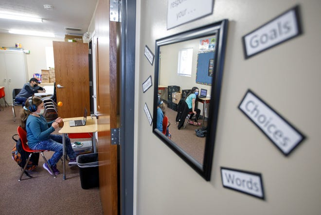 Reflected in a mirror, Maricela Rodriguez, 9, looks back to Sydney Sheline, 10, as they do schoolwork at Seven Baskets Community House, a faith-based learning extension center that helps Columbus City Schools children on the East Side.