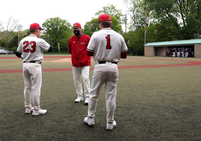 Ray Benjamin, center, talks to his sons, Michael, left, and Ryan before a recent game. Ray's father, Bob, is the school's former head coach and now is an assistant.