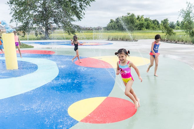Lillian Page, 4, runs past her 7-year-old sister, Landry, Tuesday at the new splash pad at the Bayou Country Sports Park in Houma.