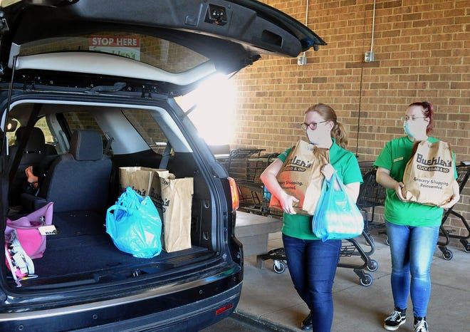 Madison Schroer and Olivia Connock, employees at Buehler's Milltown, load the back of Lindsay Sandmann's vehicle with her online grocery order. This is her second time using the service at Buehler's.