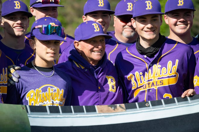Blissfield head baseball coach Larry Tuttle lifts a banner with his team following his record-breaking win Tuesday at Hillsdale.