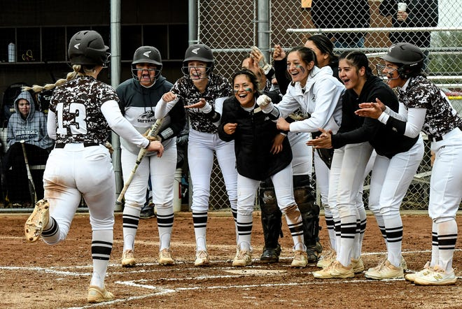 Members of the Garden City High School softball team begin the celebration as teammate Rilee McGraw (13) reaches home plate after hitting a two-run home run in the fourth inning of the second game Tuesday against Thomas More Prep at Tangeman Sports Complex.
