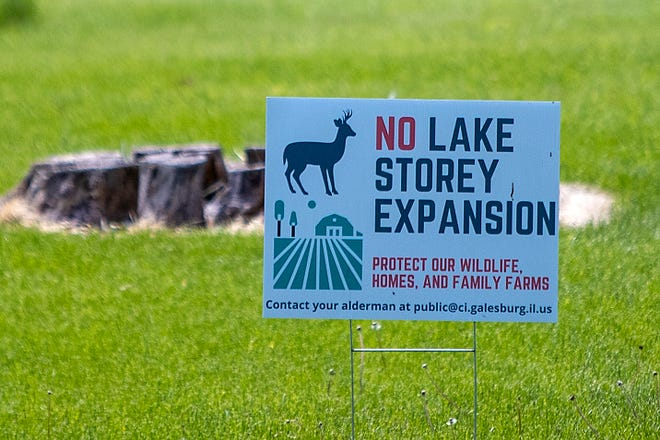 A sign protesting against the proposed expansion of Lake Storey are seen in a yard near the lake on Wednesday, May 12, 2021.