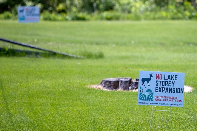 Signs protesting against the proposed expansion of Lake Storey are seen in a yard near the lake on Wednesday, May 12, 2021.