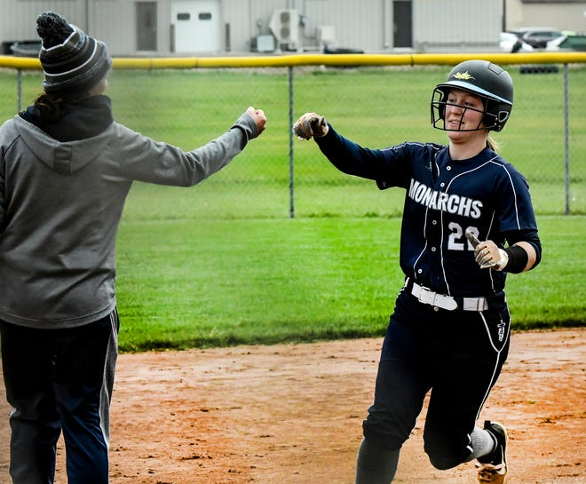 Thomas More Prep-Marian's Emilee Augustine, right, is congratulated as she rounds third base on her way to home plate after hitting a two-run home run in the third inning of the second game Tuesday against Garden City at Tangeman Sports Complex in Garden City.