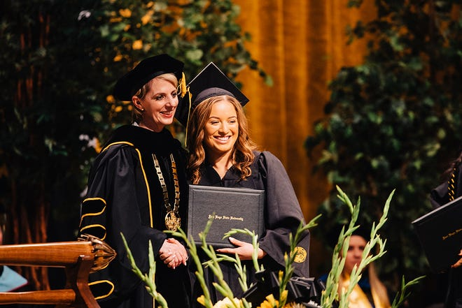 FHSU president Tisa Mason poses for a picture with a past graduate at commencement.