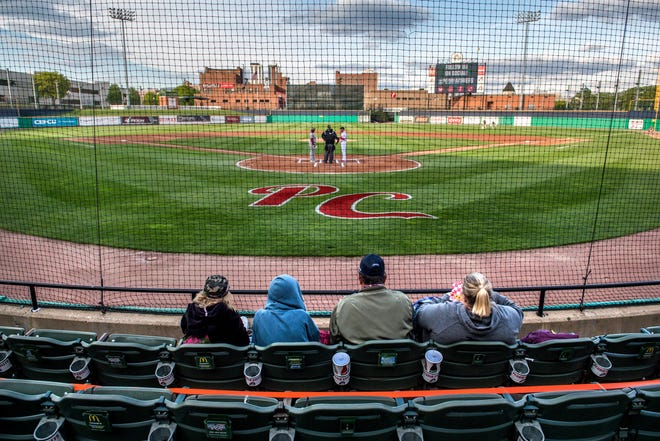 A family takes their spot in the socially-distanced stands as the managers and umpires confer at home plate before the start of the home opener between the Peoria Chiefs and the Wisconsin Timber Rattlers on Tuesday, May 11, 2021 at Dozer Park in Peoria.
