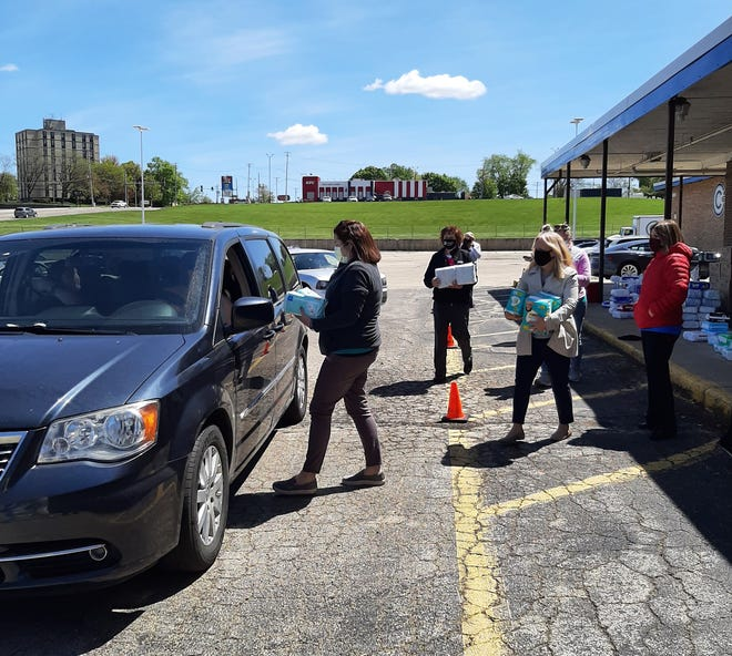 Members of the FHN Value Support Team hand out packages of diapers, baby wipes and other essentials to parents at a drive-thru event Tuesday, May 11, 2021, at the Lincoln Mall in Freeport. Donations by FHN employees funded the free event.