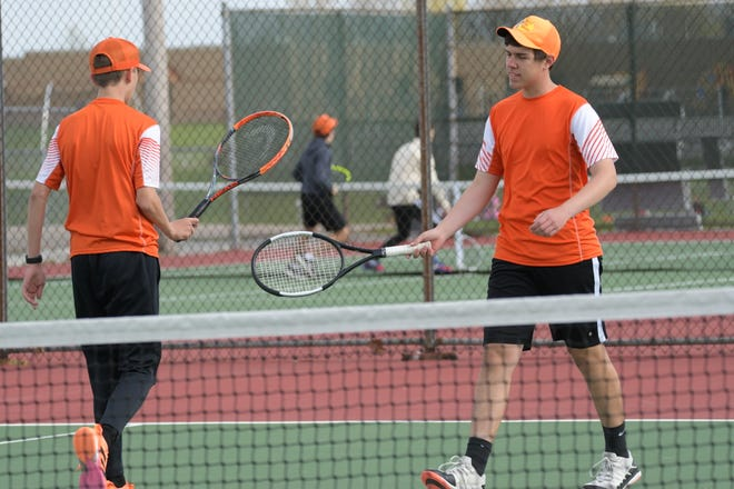 Kirksville's Gavin Pike, left, and Jacob Doman, right, go to bump rackets after scoring a point in a regular-season doubles match against Moberly.