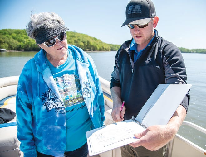 Scientist Cody Luebbering shows Missouri Master       Naturalist volunteer Carol Bullard how to fill out a lake quality study chart.