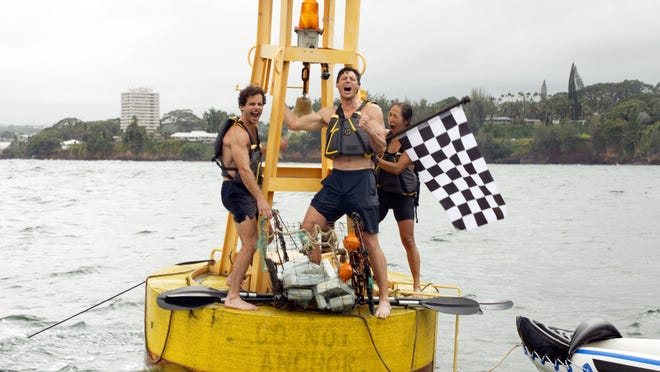 Bedford High School graduate James Batey (center), and teammates Jay Wyatt (left) and Marilina Kim (right) celebrate after reaching the finish buoy and claiming their $1 million prize for winning National Geographic's 'Race to the Center of the Earth', which aired its final episode Monday.