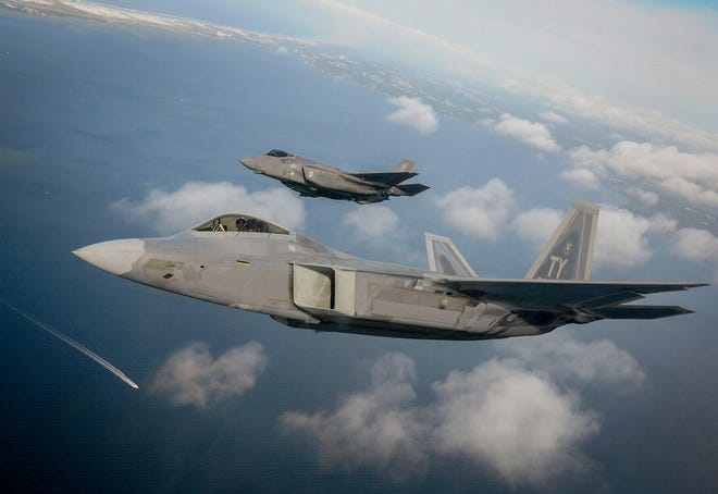 An F-22 Raptor (foreground) and an F-35 Lightning II, both like the aircraft that crashed in separate May 2020 incidents at Eglin Air Force Base, fly along the Gulf of Mexico coast.