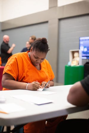 An incarcerated woman at the Oklahoma County jail writes a note to her child during Prison Fellowship's Mother's Day Teddy Bear Project on May 8 in Oklahoma City.