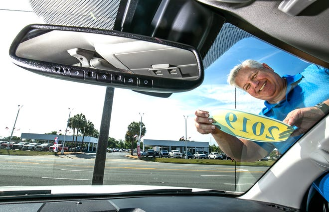 Chris Spears, owner of Prestige Auto Sales, places a 2019 sticker on a Toyota pickup truck that he has for sale on his lot Wednesday morning, May 12, 2021 at his dealership in Ocala, Florida.