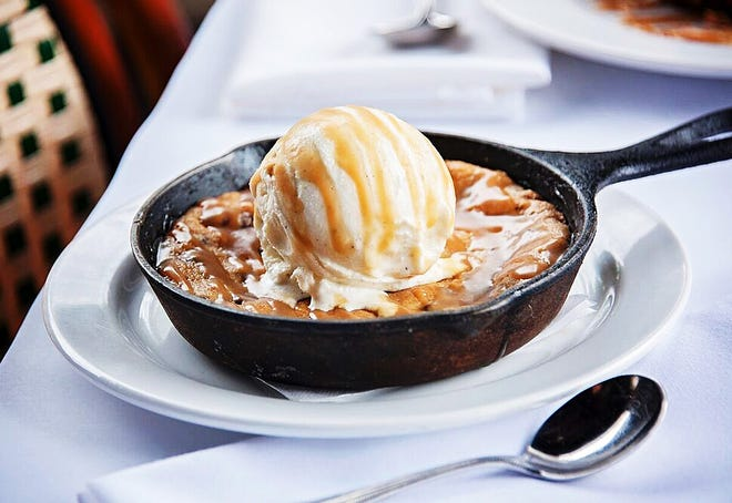 BrickTop's prepares and serves its jumbo chocolate chip cookies in a small skillet. The dessert is topped with vanilla ice cream and caramel.